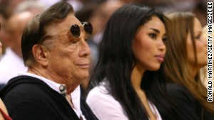 Donald Sterling and V. Stiviano sitting courtside. (Ronald Martinez/Getty Images)